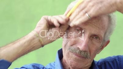 Elderly hispanic man looking and smiling at camera, brushing hair