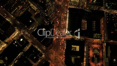 Aerial night vertical view of city street traffic, buildings, USA