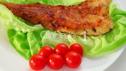 Fried fish dish - fish fillet, green salad and tomatoes dolly shot