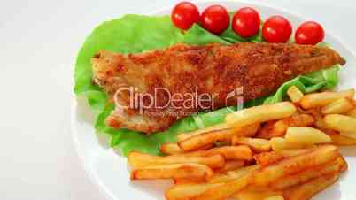 Fried fish dish - fish fillet on green salad with chips and tomatoes