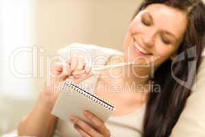 Pensive brunette woman writing to notebook