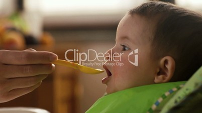 Child and nutrition, mom feeding little daughter in kitchen