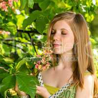 Young girl smelling blossom of the tree