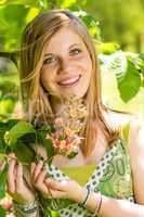 Teenage girl smelling blooming tree in springtime