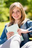 Teenage student sitting outside enjoying sunshine