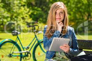 Pensive teenager in park with tablet