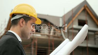 Man working, architect in construction site looking at building plans