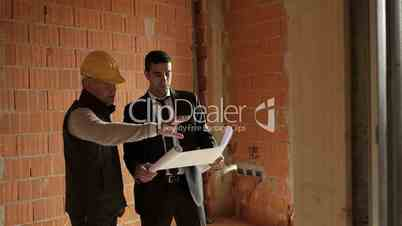 Plumber and architect talking and looking at blueprint in construction site