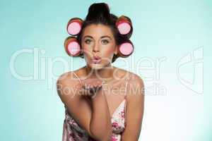 sexy woman in curlers blowing a kiss