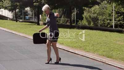Business woman with briefcase balancing on high heels on grating