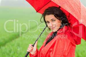 Smiling woman looking at camera during rainfall