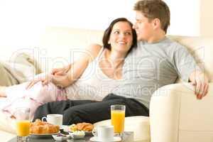 Smiling couple eating breakfast on their honeymoon