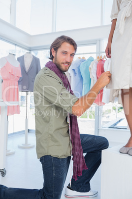 Fashion designer smiling to the camera and picking needles