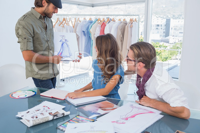 Fashion designer presenting his draw to colleagues