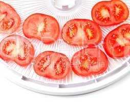 ripe tomato on food dehydrator tray, ready to dry