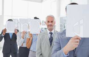 Business team covering face with white paper except for one