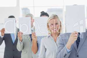 Business team covering face with white paper except for one woma