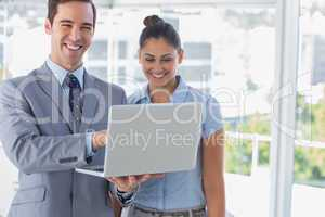 Businessman partners looking at laptop and laughing