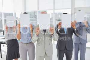 Buisness team holding up blank pages and covering their faces