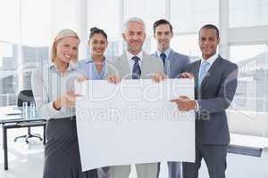 Business team holding large blank poster and pointing to it