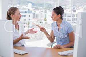 Businesswomen arguing at their desk