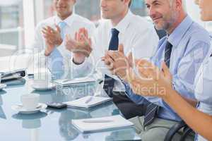 Group of business people clapping together