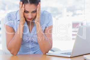 Stressed businesswoman having her head in hands