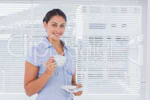 Smiling businesswoman holding coffee cup
