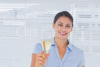 Brunette businesswoman raising a glass of champagne