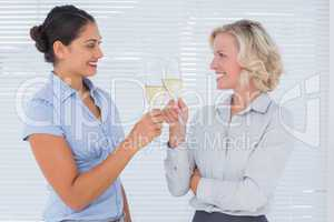 Two cheerful colleagues clinking their flutes of champagne