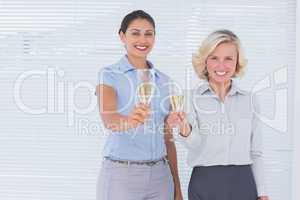 Coworkers holding flutes of champagne