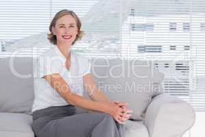 Smiling businesswoman sitting on couch