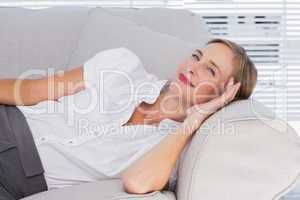 Smiling businesswoman lying on couch