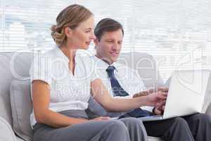 Business people watching something on laptop