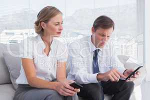 Attractive business partners sitting on couch