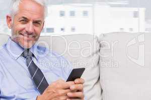 Happy businessman using smartphone