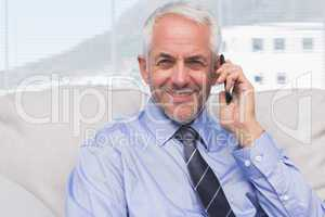 Businessman calling on smartphone and smiling at camera