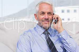 Cheerful businessman calling on smartphone