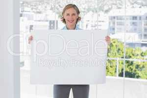 Happy businesswoman holding large white poster