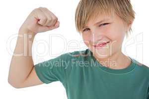 Little boy tensing arm muscle