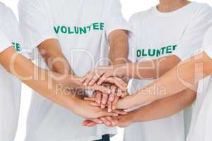 Group of volunteers putting hands together