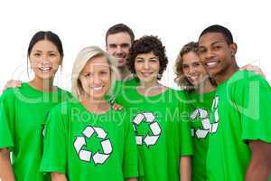 Group of smiling activists wearing green shirt with recycling sy