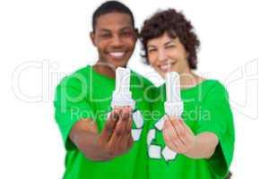 Cheerful activists holding energy saving light bulbs