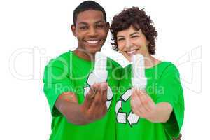 Two environmental activists holding energy saving light bulbs