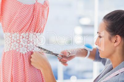 Fashion designer cutting dress
