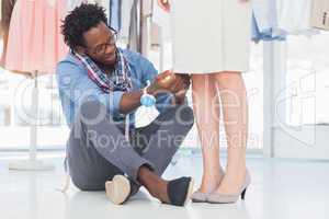 Fashion designer sitting and adjusting dress