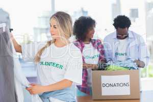 Volunteers putting clothes in clothes rail