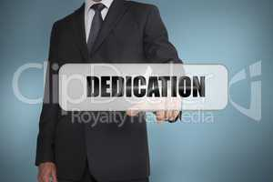 Businessman selecting the word dedication written on white tag