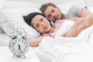 Tired couple looking at the alarm clock
