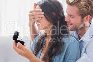 Man hiding his wifes eyes to offer her an engagement ring